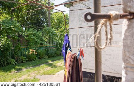 Plastic Clothespins Hang In A Row On The Rope. Rope Outdoors, On A Blurred Background In A Sunny Gar