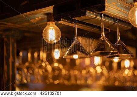 Martini Glasses Hang Upside-down In The Bar In The Warm Light Of The Restaurant