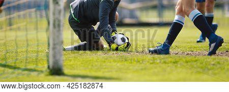 Football Goalkeeper On Knees In Action Catching Ball. Goalie Saving Goal. Horizontal Soccer Backgrou