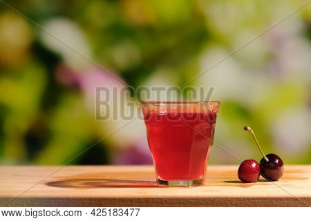Glass Shot Of Cherry Liqueur Outdoors. Berry Alcoholic Drink On Natural Summer Background.