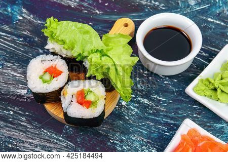 Vegan Sushi Rolls With Avocado, Cucumber Salad And Tomato Black Background. Healthy Vegan Food Conce