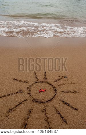 Figure Of A Red Plane And Painted The Sun On The Sand On The Coast. Rest And Tourism By Plane To The