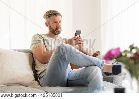 Shot Of Handsome Man Sitting On The Sofa At Home And Text Messaging.