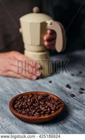 a young caucasian man is preparing some coffee in a beige moka pot, sitting at a gray rustic wooden table and some roasted coffee beans in the foreground