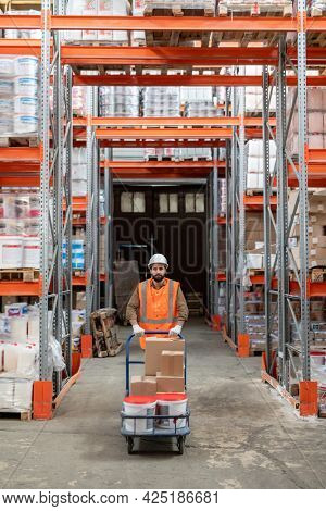 Warehouse engineer in workwear moving forwards between racks