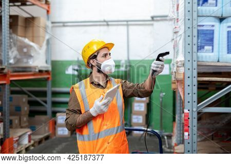 Young engineer in workwear using scanner for checking information about packed goods
