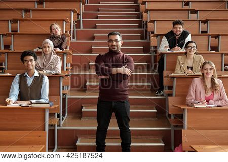 Successful teacher standing against group of students in auditorium