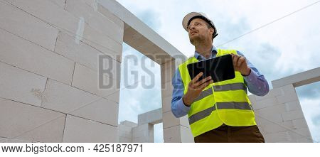 Construction Project Monitoring - Engineering Supervisor Working With Digital Tablet At Building Sit