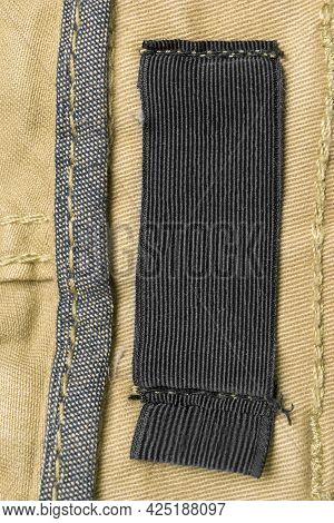 Blank Textile Clothing Label On Yellow Textile Background Closeup