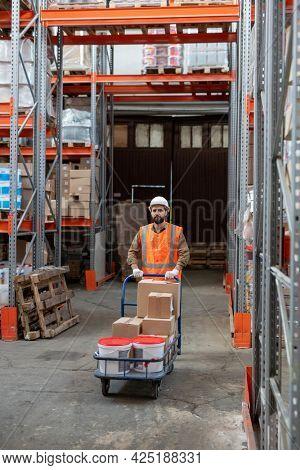Loader in workwear pushing cart with goods while walking along racks