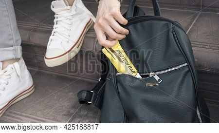 Close-up Of A Girl Crouched On The Steps For A Light Snack. She Pulls A Protein Bar Out Of Her Women