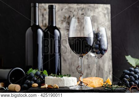Red Wine In Classic Glass With Wine Bottles Composition. Elegant Wine Bar Menu With Snacks Cheese On