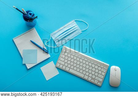 Back To School Layout Concept. Blue Work Desk With Covid Medical Face Mask, Writes Notes, Notebook K