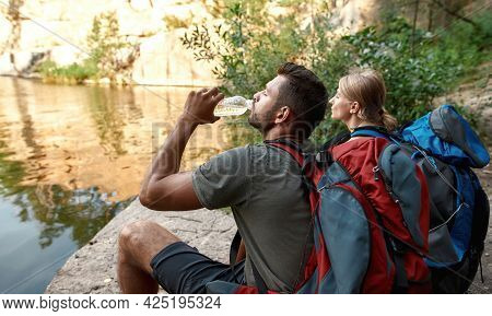 Young Caucasian Pair Drinking Water During Halt In Summer Nature Near Lake, Widescreen. Hiking, Trav