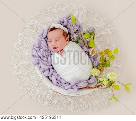 Portrait of little beautiful newborn baby girl swaadled in fabric and wearing wreath with flowers sleeping and smiling in basin with decoration during studio photoshoot. Cute infant child