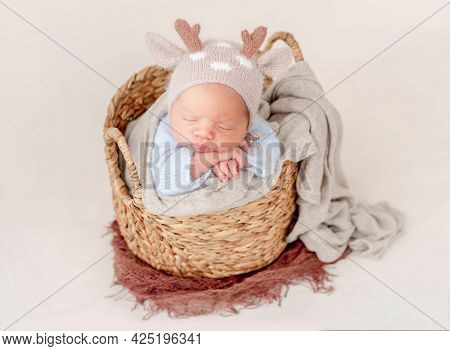 Portrait of newborn baby boy wearing knitted hat with deer horns sleeping on his tummy in basket and holding tiny hands under his cheeks. Adorable infant child napping in studio