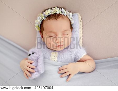 Beautiful little newborn baby girl wearing knitted costume and wreath with flowers holding toy in her tiny hands and sleeping under blanket in studio. Cute infant child napping