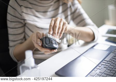 Young Woman Wiping Computer Mouse With Disinfectant Wipe While Working From Home