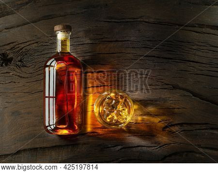 Bottle of whisky and glass of whisky on wooden board. Top view.