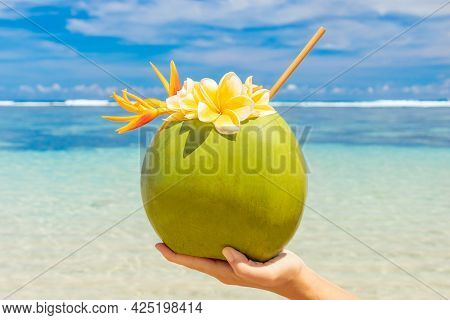 Coconut Drink In A Female Hand On A Tropical Beach