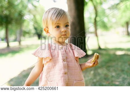 Little Girl With A Pancake In Her Hand Stands On A Green Lawn
