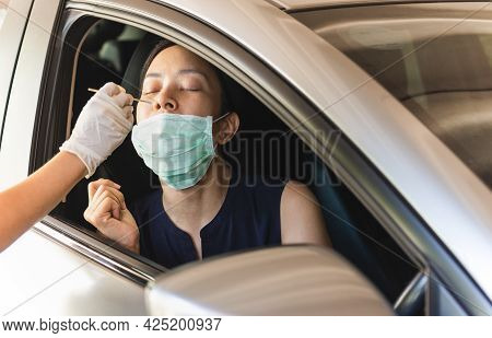 Medical Worker Taking Nasal Swab From Woman In Car To Test For Covid-19 Infection
