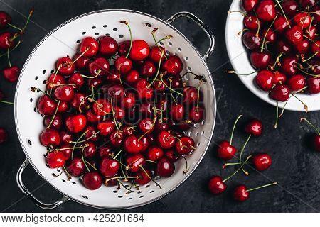 Cherry. Sweet Cherries In White Colander On Dark Stone Concrete Background. Ripe Sweet Red Cherries.