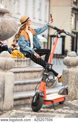 Young Woman, Sitting On Staircase Of Old Historical Building In City Center, Taking Picture With Her