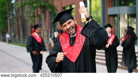 School Graduate Man In Academic Gown And Hat Looking At The Camera With Happy Smile. Happy Multiraci