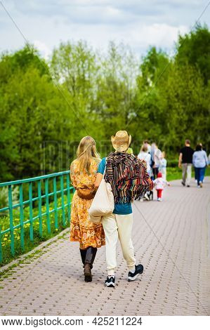 Unrecognizable Walking Young Couple In Straw Hats, Rear View, Summer Day In Park. Concept Of Romanti