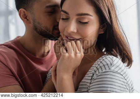 Young Man Kissing Smiling Girlfriend With Closed Eyes And Hands Near Face In Kitchen