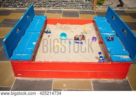 Empty Playground In A Park On A Sunny Day. Empty Sandbox With Toys
