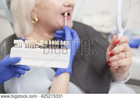 Selective Focus On Teeth Whitening Shade Chart In The Hand Of Dentist, Senior Woman Looking In The M