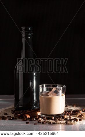 A Glass Of Irish Cream Coffee Liqueur With Ice And Ice. Coffee Beans, Black Bottle.