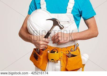 Crop Unrecognizable Workman In Overall With Hardhat And Professional Toolkit On Waist Holding Hammer