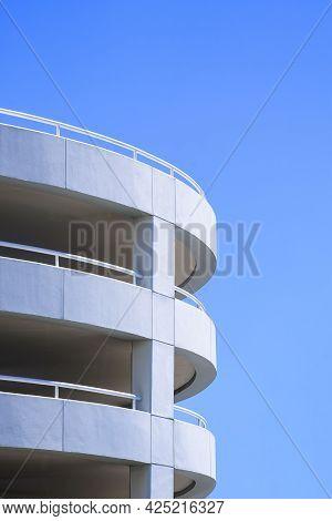 Spiral Ramp Of Parking Garage Building Against Blue Sky Background In Vertical Frame
