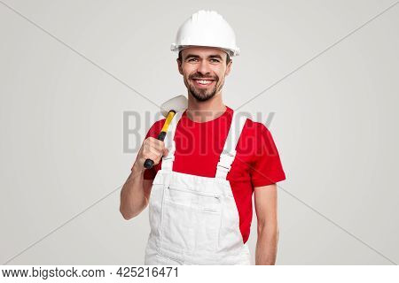 Confident Professional Male Contractor In Workwear And Hardhat With Hammer In Hand Smiling And Looki