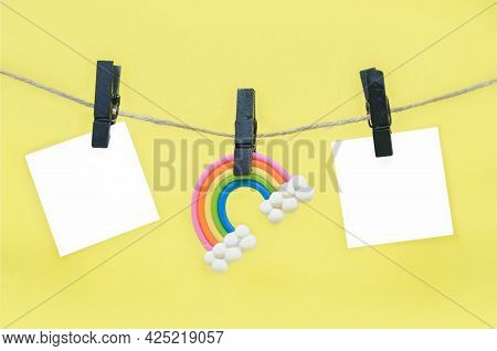 Rainbow Figurine And Blank Note Sheets Attached To Rope With Black Wooden Clothespins Against Yellow
