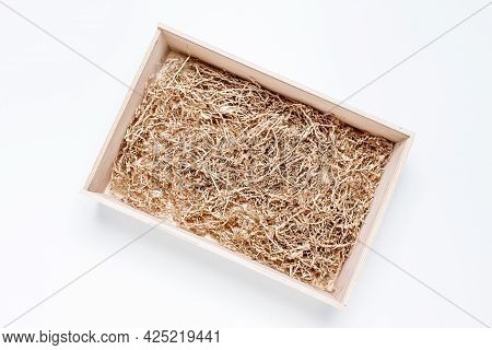 Opened Gift Wooden Box With Shredded Paper Filler On White Background For Product Placement. Top Vie