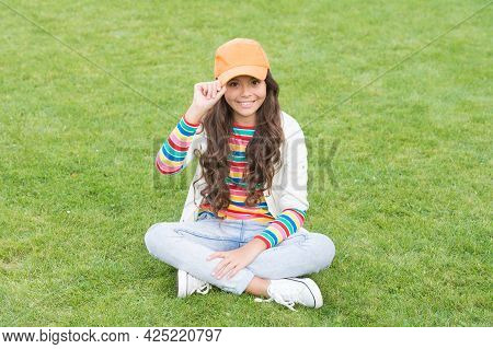 Hip Hop Girl. Happy Girl Child Sit On Green Grass. Childhood And Girlhood. School Education