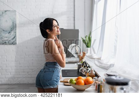 Cheerful Young Woman Standing Near Bowl With Fresh Fruits In Kitchen