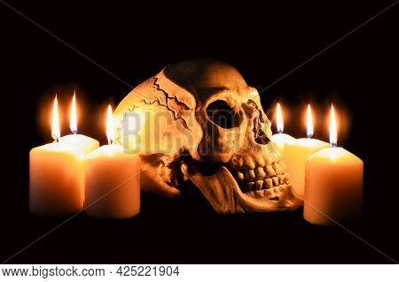 Human Skull In Profile Among Burning Candles In The Dark, Scary Still Life, Altar