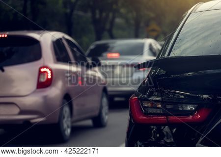 Rear Side Black Car On The Road. Traveling In A Traffic Jam. Park In A Row On Two Lanes. Car Turn On