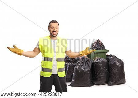 Waste collector posing in front of a bin and a pile of bin bags isolated on white background