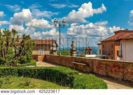 Green bushes in the park and typical houses under beautiful blue sky with white clouds in small town of Govone in Piedmont, Northern Italy.