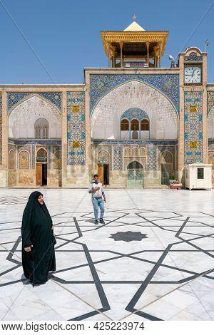 Qom, Iran - 04.20.2019: Islamic Woman In Tradiitonal Black Dress Walking Under In The Courtyard Of F
