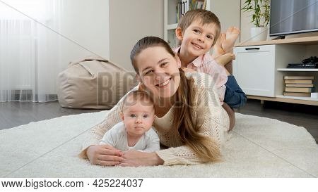 Happy Smiling Children Hugging And Having Fun With Mother On Carpet In Living Room. Parenting, Child
