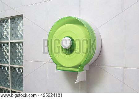 Green Plastic Toilet Tissue Paper Roll Holder With White Tissue Paper On The Tile Wall In The Bathro