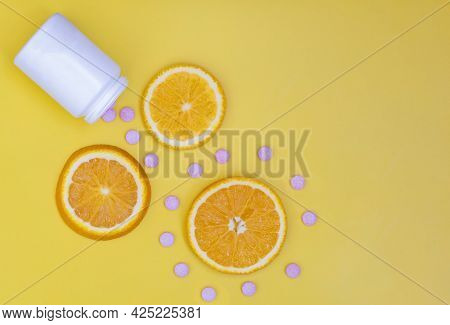 Vitamin C. Orange Slices On A Bright Background And Vitamin C Tablets. The Layout Of The Branding Of