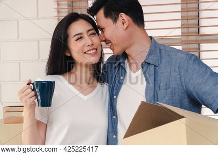Happy Young Couple Carrying Cardboard Boxes And Walking From The Front Door Into The House In A New